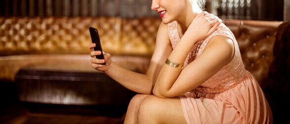 ケータイを触っているドレス姿の女性